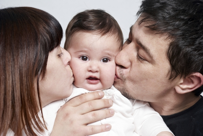 New dad and mom kissing baby on cheek