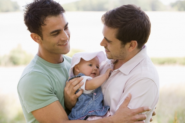 Two men holding baby girl